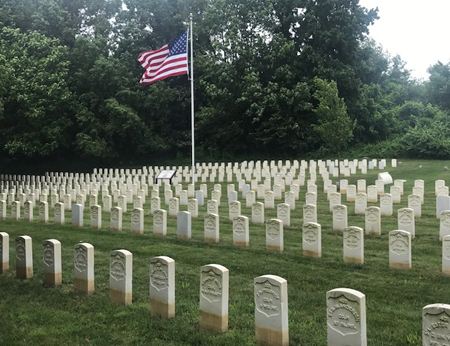The American flag waves over headstones at the Mount Moriah Cemetery Soldiers' Lot.
