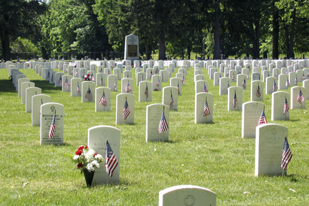 Photo of headstones adorned with American flags at Woodlawn National Cemetery.