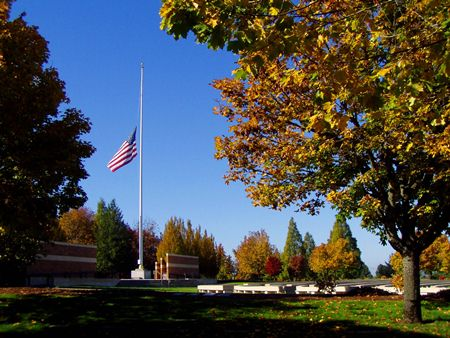 A photo of Willamette's assembly area in the fall with a U.S. flag at half staff.