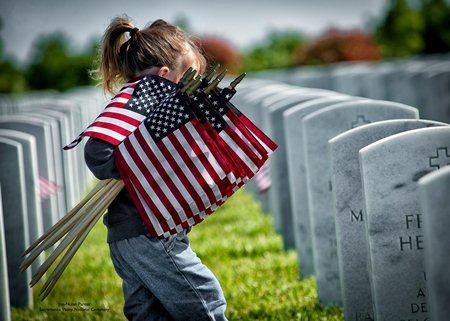 Young girl places Memorial Day flags at Sacramento Valley National Cemetery.