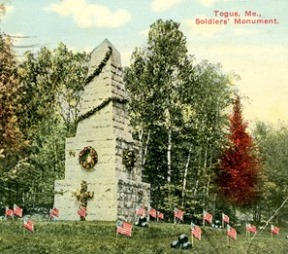 Vintage color view of monument (Soldier's Monument, Togus, Maine) decorated for Memorial Day, small US flags placed on ground.