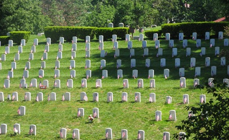 "Overall view of Evergreen Cemetery Soldiers' Lot showing several rows of government headstones in the background and a section marker engraved with ""U.S."" in the foreground."