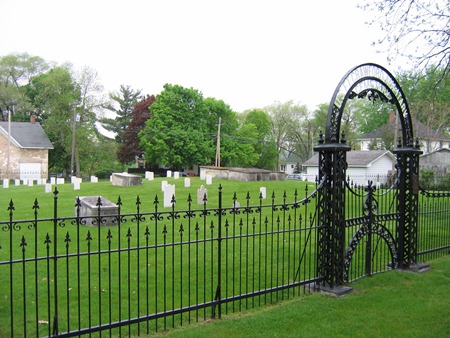 View of fence and arched entrance gate at Fort Crawford Soldiers' Lot; both government and private headstones, including several box tombs, are in the background.