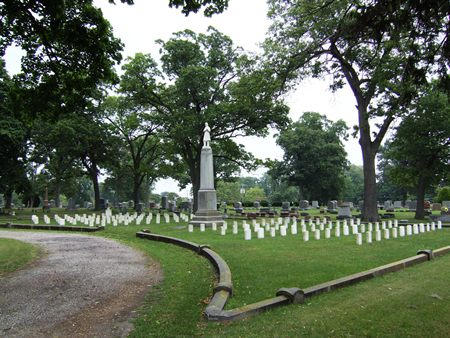 Overall view of Lakeside Cemetery Soldiers' Lot surrounded by low, concrete curbing.  At the center of the lot is the 'Unknown Soldier' monument on either side are rows of government headstones.