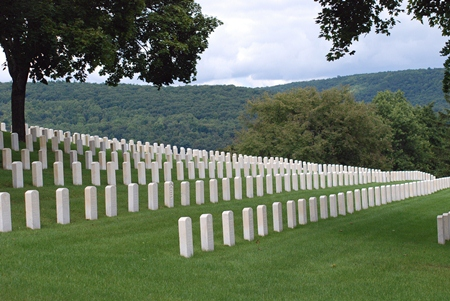 A photo of upright headstones closely aligned in rows among the grounds.  Trees with autumn leaves and a mountain range sits in the background.