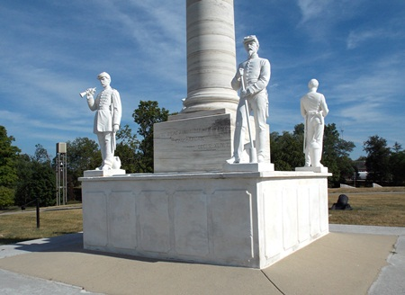 Photo of a tall white marble monument with four small male figures at each corner of the square base. A larger male figure stands at the top of the pillar.
