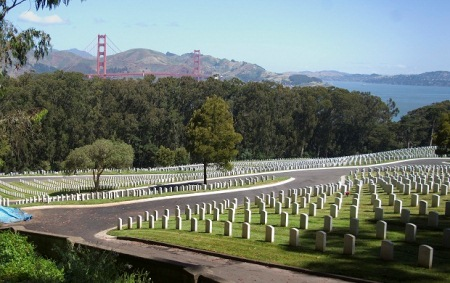 Photo of a hill covered with several rows of upright headstones and the San Franciso bridge hovering above the trees in the background.