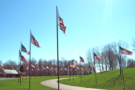 A photo of a two winding cement roads dividing green lawns lined with American flags.