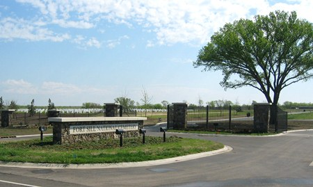A photo of Fort Sill's entrance gate. A rectangular cobble-stone wall that stands alone on an oval-shaped grass meridian.  Opened iron gates leads into the cemetery with upright markers shown in the background.