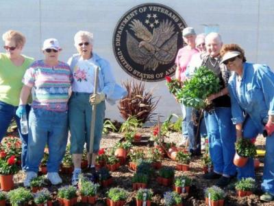 volunteers plant flowers at cemetery entrance